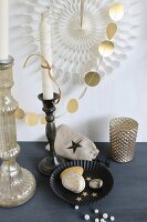 Christmas arrangement of gold-painted pebbles in black cake tin, white candle in candlestick and garland of gold paper discs