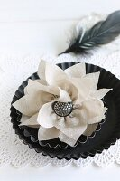 Hand-sewn silk flowers and silver button in flan tin on doily with black feather in background
