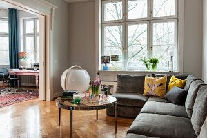 Corner sofa and round coffee table on herringbone parquet floor in pale grey living room