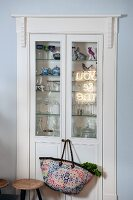 Fitted, glass-fronted cabinet with shopping bag hung from door knob