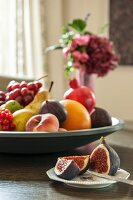 Cut figs on plate and various fruits in large fruit bowl