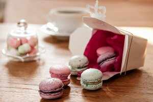 Colourful macarons tumbling onto wooden table from gift box