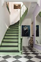 Wooden staircase painted pastel-green and black in period hallway with chequered floor and racing bike leaning against wall