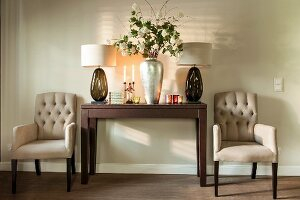 Armchairs flanking table lamps and silver vase of white flowers on side table
