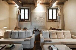 Elegant white sofa set and matching ottomans in renovated rustic living room