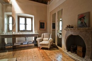 Spacious bathroom with pale armchair and fireplace