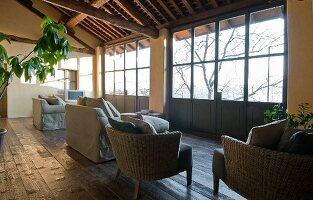 Wicker armchairs and sofas with pale grey loose covers on rustic wooden floor next to glazed terrace doors