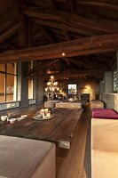 Interior with exposed wooden roof structure, upholstered benches and coffee table with board top
