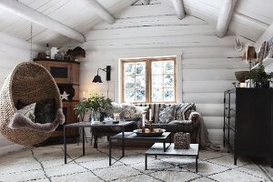 Hanging chair in cosy living room in log cabin