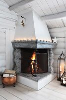 Fire in open fireplace and decorative candles in log cabin
