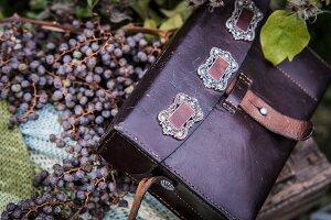 Purple leather bag on berries