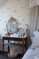 Romantic arrangement of candlestick, ornate picture frame and table lamp with lace lampshade on bedside table