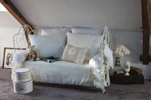 Vintage-style lace cushions on white metal couch with ornate frame