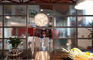 View through industrial-style glass sliding doors to dining area with spherical chandelier in loft apartment