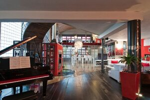 Open grand piano in open-plan loft apartment with white and red furnishings