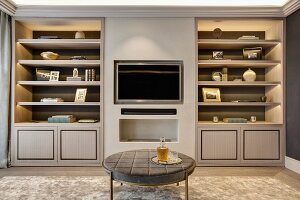 Round table in front of flatscreen TV recessed in wall between fitted cupboards and shelves