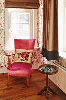 Floral scatter cushion on pink velvet armchair next to delicate, antique, wooden side table below window in corner
