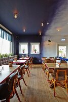 Wooden table and leather chairs in restaurant with blue wall