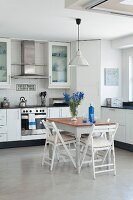 Small dining table and folding chairs in modern fitted kitchen with bouquet and bottle providing blue accents