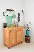 Nostalgische Kaffeedose und Küchengeschirr auf bäuerlicher Kommode, an Wandhakenleiste aufgehängtes Geschirr