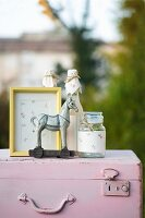Yellow picture frame, preserving jar, bottle decorated with floral paper and horse figurine on top of pink vintage suitcase