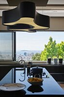 Black glossy kitchen counter in front of large windows with view of city and sea