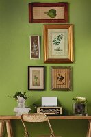 retro typewriter and bust below framed botanical illustrations on green wall