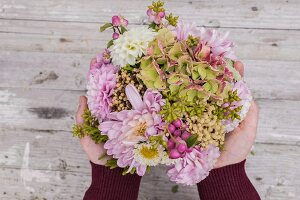 hands holding arrangement of chrysanthemums, dahlias and hydrangeas