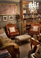 Antique-style sofa and armchairs around ottoman below chandelier in living room