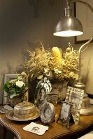 Vintage arrangement of family photos in antique silver frames and retro table lamp on side table
