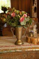 Bouquet in brass trophy-shaped vase