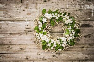 Wreath of snowberries on rustic wooden surface