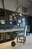 Custom wooden table with metal frame, upholstered vintage chairs, collection of pictures and basket ball hoop on wall