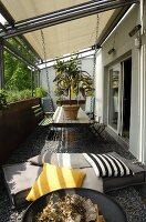 Floor cushions, scatter cushions, fire bowl, dining table and chairs under awning on balcony with pebble floor