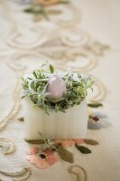 Easter nest made from china egg and green plant in alabaster pot on embroidered vintage tablecloth