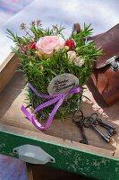 Gesteck aus Rosen, Nelken und Kräutern als Geschenk