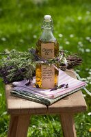 Bottle of oil decorated with posy of herbs on wooden stool