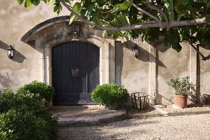 Potted shrubs flanking front door below curved porch of grand Mediterranean country house