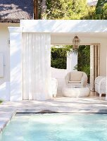White wicker furniture in elegant summery lounge area next to pool