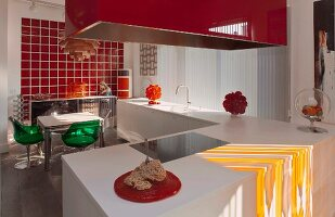 White kitchen counter, red extractor hood and dining table and chairs in front of red glass wall tiles in open-plan kitchen
