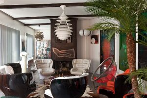 White leather armchairs and black plastic shell chairs below classic pendant lamp in open-plan retro interior