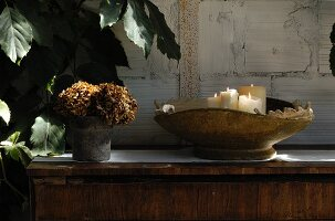 White candles in vintage bowl and pot of dried flowers