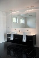 Washstand with twin countertop sinks below mirror in black and white designer bathroom