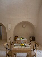 Wooden chairs at set table in Mediterranean dining room of Apulian trullo