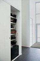 White fitted cupboard with view of shoe shelves through open sliding door in modern hallway