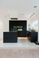 Black designer kitchen with white floor tiles in open-plan interior