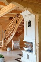 Custom staircase with carved balustrade and wood-burning oven in solid wooden house