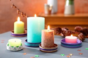 Colourful candles in saucers made from jar lids