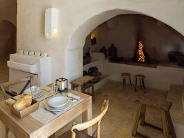 Set table next to open fire in arched niche with masonry shelves and platforms in Apulian trullo