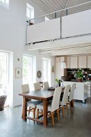 Wooden table and pale upholstered chairs in dining area of open-plan kitchen below white gallery